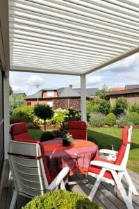 1500 Series Outdoor Shelter above a deck in a backyard garden