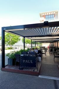 2000 Series Outdoor Shelter covering an outdoor dining area at PAUL