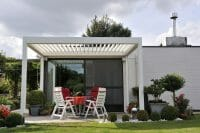 1500 Series Outdoor Shelter above a patio in a backyard garden