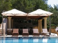 P6 Square Uno Umbrellas shading some pool chairs by a pool