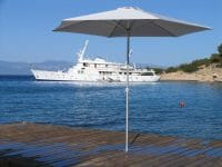 P50 Umbrella on a dock in Greece with a yacht on the water in the background