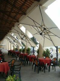 Veneto Cantilever Umbrellas tilted at an outdoor dining area