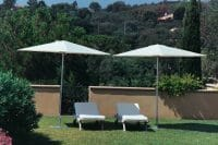 Two P50 Umbrellas shading reclined pool chairs on grass