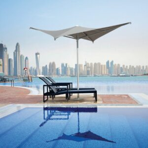 Voilá Umbrella - Taupe providing shade to beach chairs next to a large pool