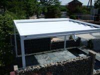 a closed roof Retractable Roof Poolside Cabana surrounded by a retaining wall