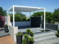 an elevated Retractable Roof Poolside Cabana behind a small pond and surrounded by retaining walls