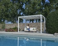woman sitting and reading a book under a closed roof Retractable Roof Poolside Cabana, next to a pool
