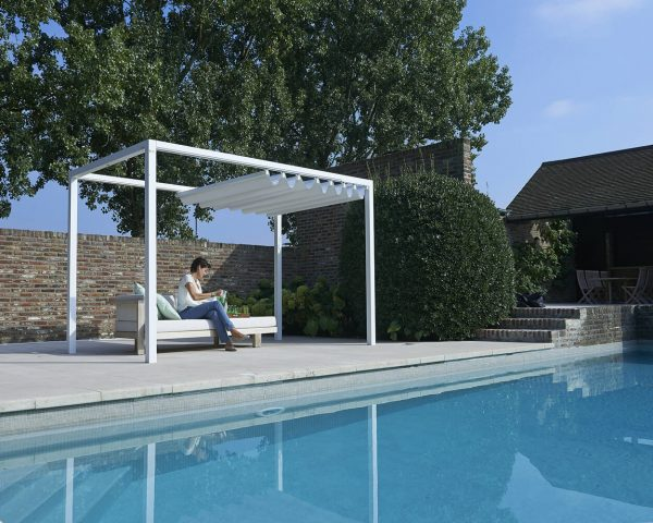 woman sitting under a Retractable Roof Poolside Cabana with a partially open roof