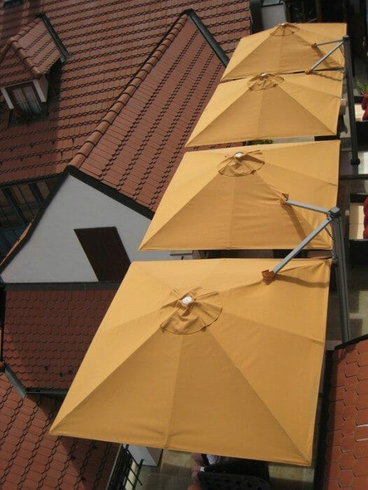 looking down on 4 p6 square duo umbrellas above a rooftop deck