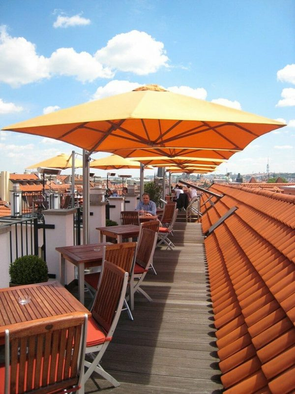 p6 square duo umbrella covering small tables on a rooftop dining area