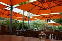Orange P6 Square Quattro Umbrellas at an outdoor dining area