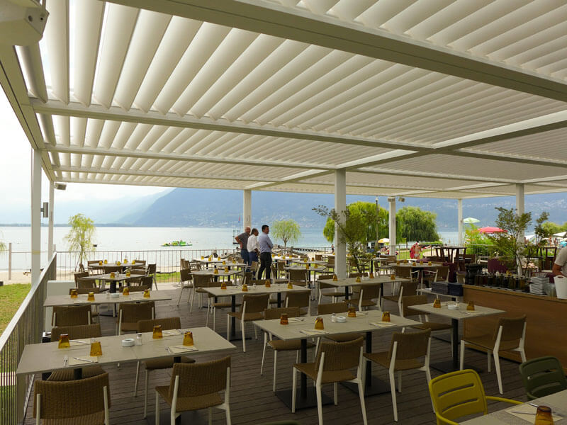 an outdoor shelter over an open air bar and restaurant next to the water
