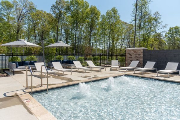 p6 square uno umbrellas covering an outdoor sofa next to a pool