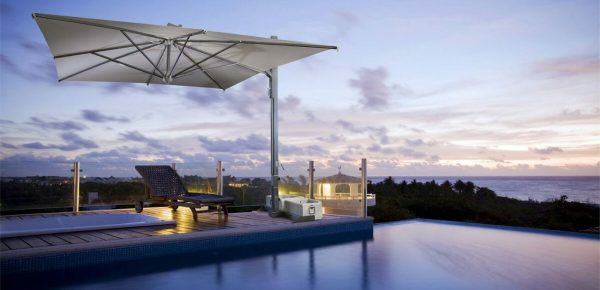 cantilevered umbrella next to an infinity pool by the ocean